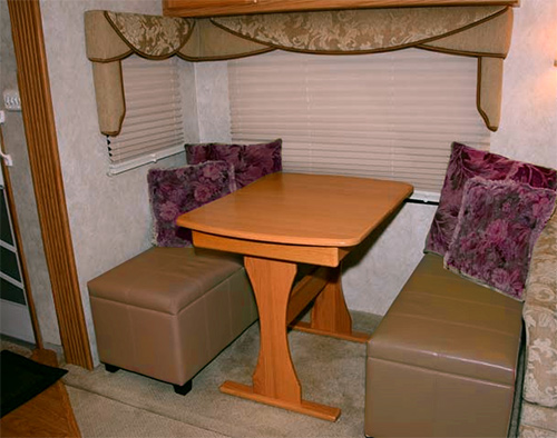 Dining area inside a Fifth Wheel with an Ottoman added for seating